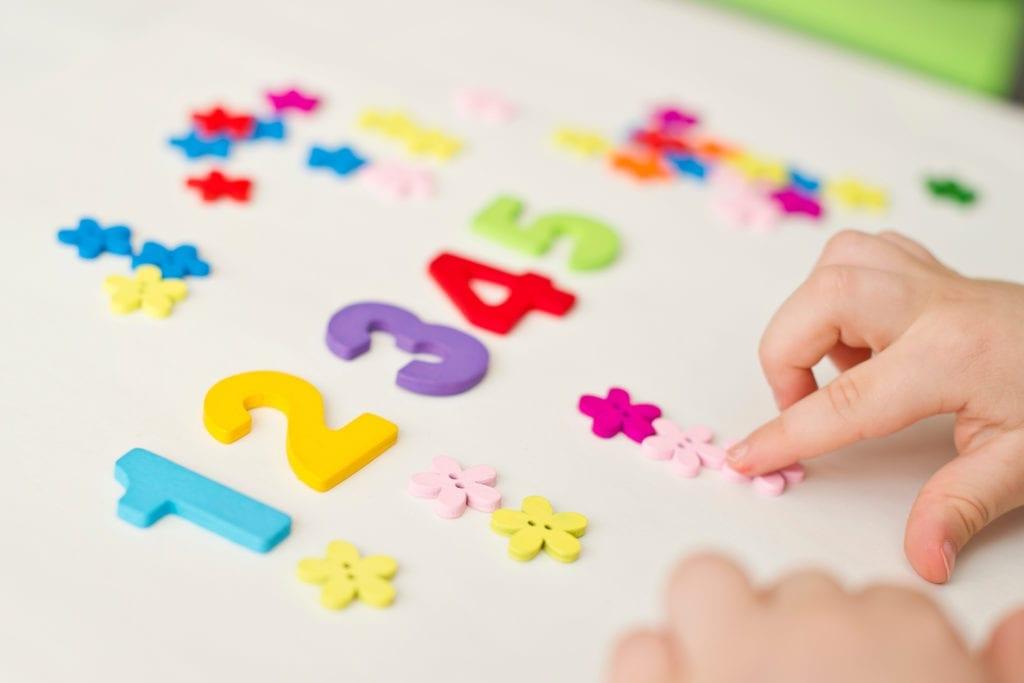 Mani di bambino che giocano con forme geometriche e numeri colorati