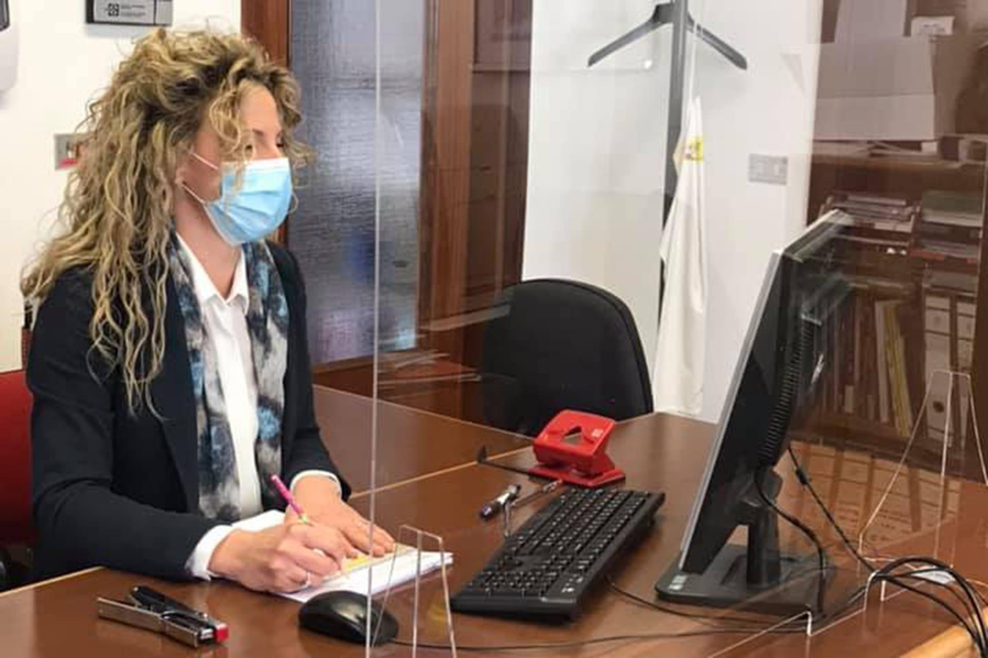 Segretaria che svolge il suo lavoro in ufficio davanti al pc protetta con apposito schermo protettivo per il pubblico