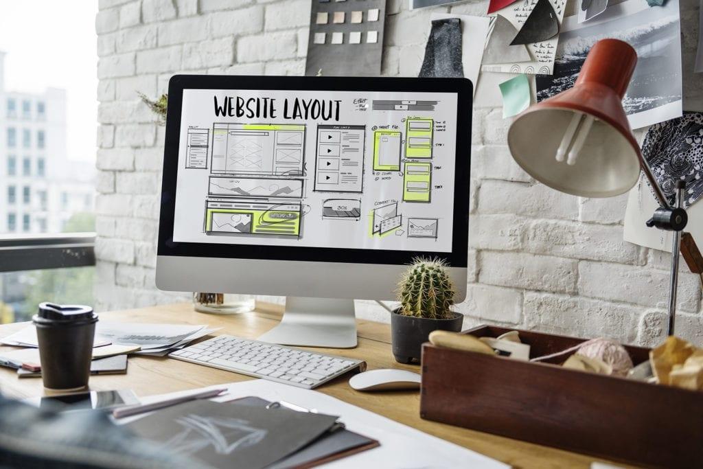 Scrivania da ufficio con computer, appunti vari, quaderni, lampada e caffè